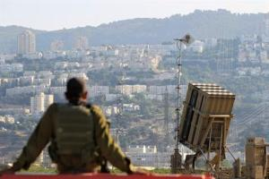 An Israeli soldier is seen next to an Iron Dome rocket interceptor battery deployed near the northern Israeli city of Haifa, AP photo