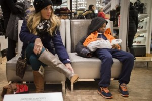 A young boy waits in the shoe section as a customer tries on a pair of boots at the Macy's Herald Square flagship store, Thursday, Nov. 28, 2013, in New York. Instead of waiting for Black Friday, which is typically the year's biggest shopping day, more than a dozen major retailers are opening on Thanksgiving this year. (AP Photo/John Minchillo)