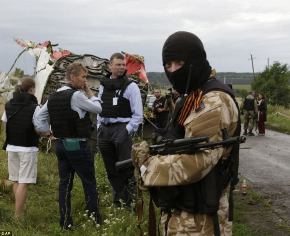 Pro Russian Separatist watches as OSCE tries to gather information on the crash.
