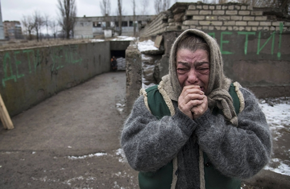 Ukrainian woman cries as she is alone after a friend leaves war area on a bus.