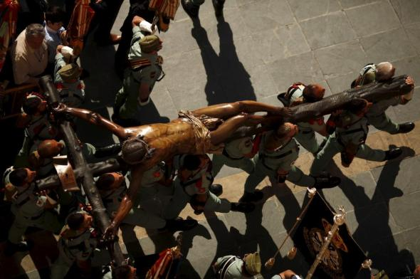"Spanish legionnaires carry statue of Christ of Mena during a ceremony before ""Mena"" brotherhood procession in Malaga"
