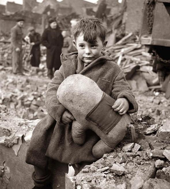 Boy holds his stuffed animal after bombing of London in WWII