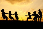 Silhouette, group of happy children playing on meadow, sunset,summertime