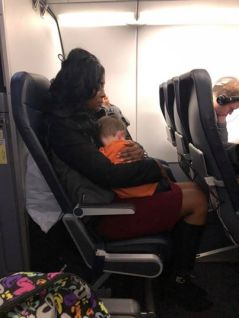 woman holds boy for mother on airline